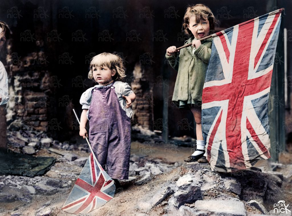 Colourised WWII photo of two small girls waving their flags in the rubble of Battersea on VE Day 1945